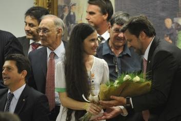 Yoani recebe flores com Bolsonaro ao fundo
